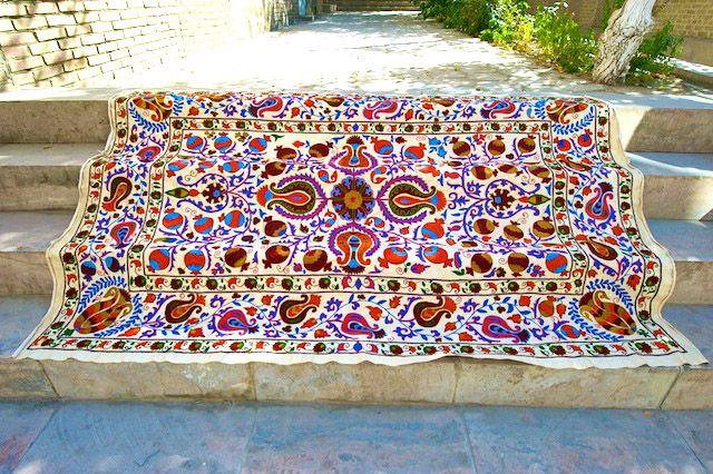 Garden of Eden SILK ON COTTON  Deze Suzanikleden uit Oezbekistan worden gemaakt door de vrouwen in de familie om te worden meegegeven als cadeau voor de bruidsschat. Men begint er vaak bij de geboorte van een dochter al aan. Het zijn prachtige kleden, als wandkleed, plaid over de bank, als sprei of tafelkleed. Deze suzani heeft een afbeelding van de levensboom, puur zijde op katoen en met een haaknaald geborduurd, de optimale vorm van borduren.