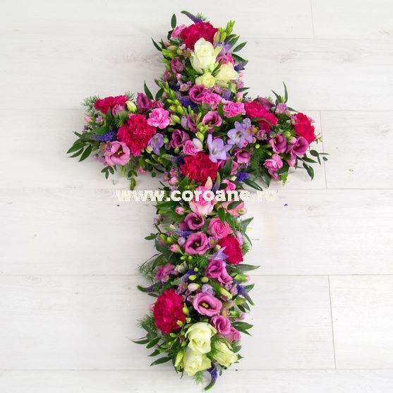 Cruce florala realizata din trandafiri, frezii si lisianthus, in diverse nuante de roz. Livrare cruce florala oriunde in Romania, comanda acum simplu si rapid cele mai proaspete flori in aranjamente funerare exceptionale.