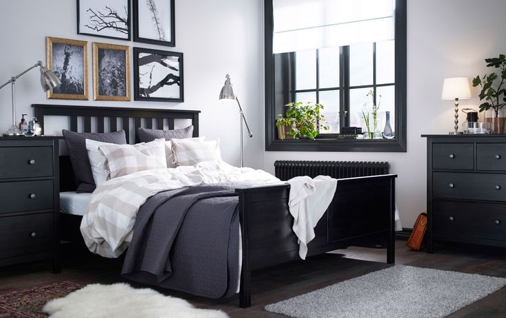 A large bedroom with a black-brown bed with bed textiles in beige/white and dakr grey. Combined with black-brown chest of drawers and lamps in nickel-plated steel.