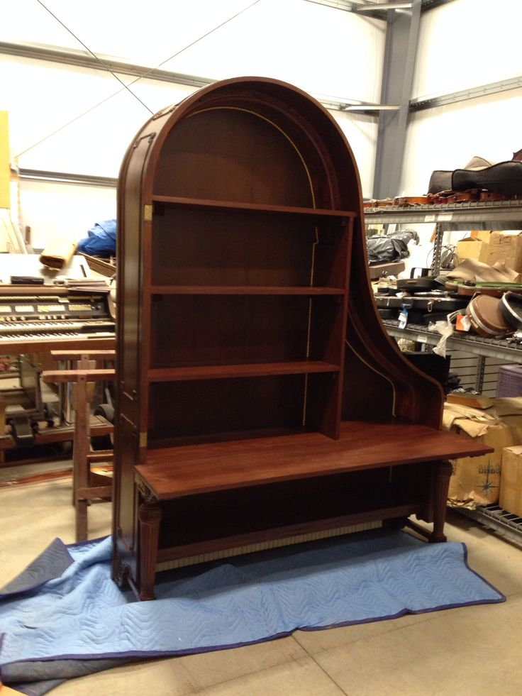 This is an old grand piano that has been gutted, refinished, and given new life as a stunning bookshelf!