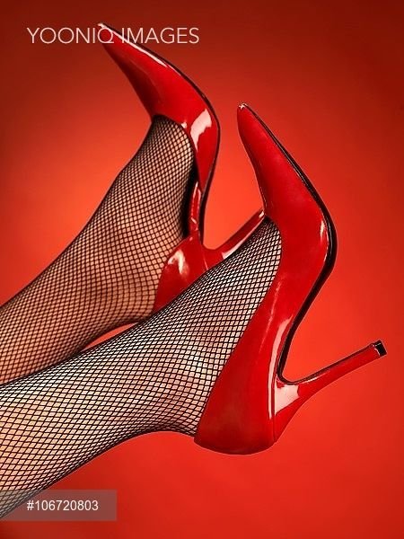 ede0bc79708 Close-up of woman's legs wearing sexy red high heel shoes and black ...