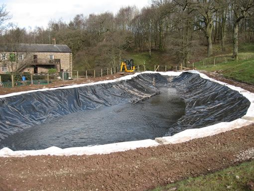 large pond liner installation the excavated pond is