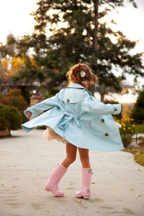 adorable, stylish little girl. pale pink rain boots and a baby blue rain coat.