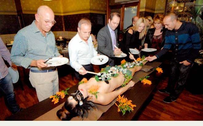 """Un grupo de comensales toma sushi del cuerpo desnudo de una modelo, en la degradante """"degustación"""" organizada por El Casino de Las Palmas."""