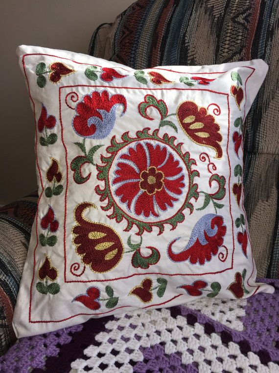 """True to the """"needle"""" origin of the Persian word suzani, these pillows are embroidered with traditional floral motifs in richly coloured patterns that define this historic style. Suzani comes from the Persian word for needle, and the word refers to embroidered hangings or fabric coverings, generally a meter and a half wide (4-5) but sometimes much more. The birthplace of suzani is in what is now Uzbekistan, the area along the Silk Roads that interconnected the cultures of Europe, Turkey and…"""