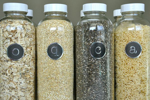 Organize dry food goods in repurposed glass drink containers.  I would love to cut out vinyl labels with my cricut.  Or even use the chalk paint idea, so relabeling would be easy.