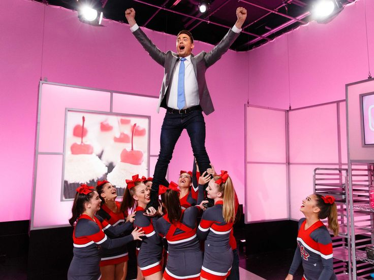 Give Me a C-A-K-E : Jonathan Bennett showed off his strength with a little help from on-set cheerleaders.