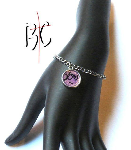 Bracelet breloque Jésus lilas  Bracelet ajustable chaîne en acier inoxydable Breloque en métal alliage Dimension 14 mm Couleur argent antique avec design Couleur lilas écrit Jésus à la main avec peinture noir. Le tout recouvert de résine