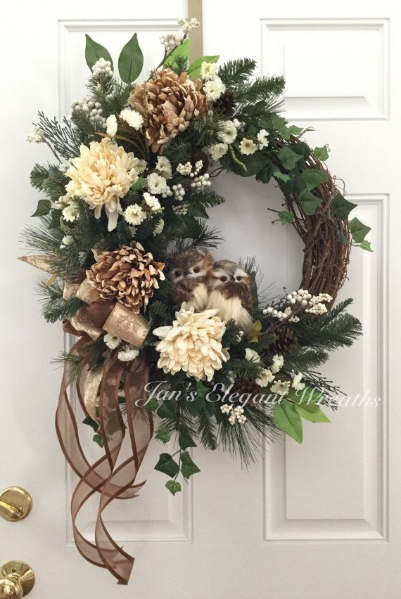 This beautiful wreath can be used for Fall and all through the Winter months!  It is a symphony of neutrals which will make it gorgeous on any color door or wall. This wreath would beautify any room in your home as well as your front door!  Your eyes will be drawn first to the two adorable little Owls. I just love them and Ive named them Herbert and Henrietta! They seem quite at home sitting on the evergreen branches. :-). Their feathers are cream and light brown in color. There are 4 large…