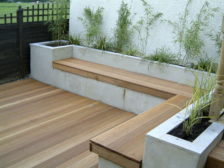 Love this built in corner bench with wooden seating and planting
