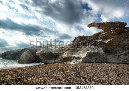 Reef at Cabo de Gata, Spain. Seascape with reef, clouds and beach