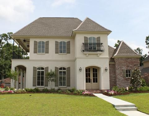 Chateau Lille Stucco with taupe shutters black wrought iron cream doors white washed brick