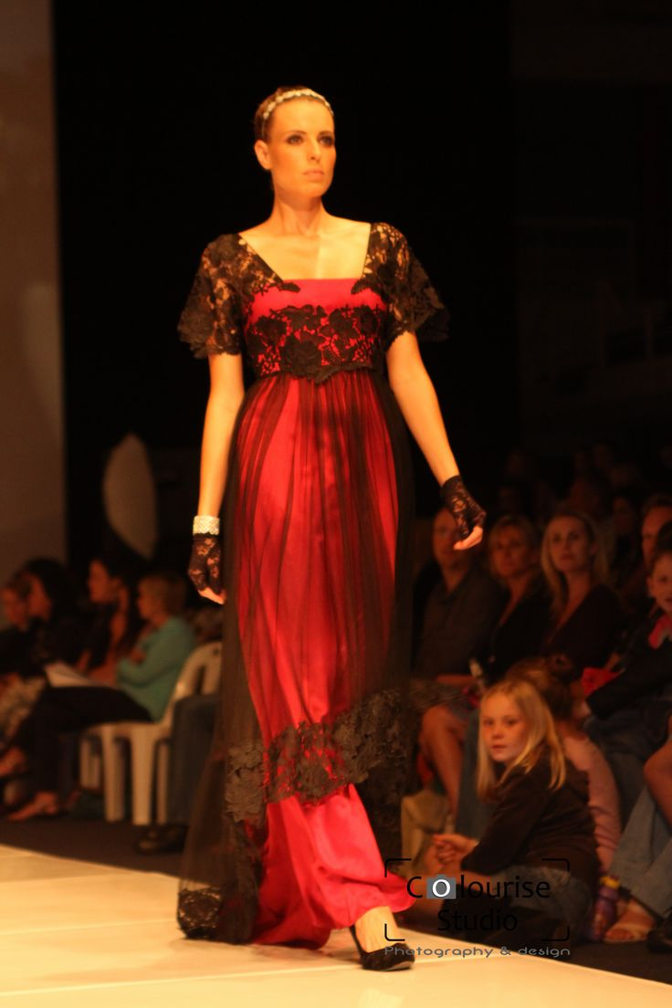 A court inspired gown of wine red silk satin and black tulle. The tulle features a border of guipure lace and the bodice features sleeves and a waistband of the same lace.