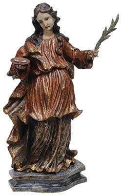 """ANTONIO FRANCISCO LISBOA, o ALEIJADINHO (1738 - 1814)  Santa Luzia .Imagem brasileira, esculpida em madeira, policromada. Minas Gerais. Séc. XVIII. A imagem tem movimento barroco ilusório, curva em """"S"""", rosto típico, com expressão serena e grave. Olhos amendoados, hipertelorismo, nariz longo e afilado, cabelos estriados em rolos sinuosos, gola cônica múltipla. Panejamento esvoaçante e rico. Rosto típico, topetes bipartidos na testa, olhos amendoados, meio-sorriso enigmático."""