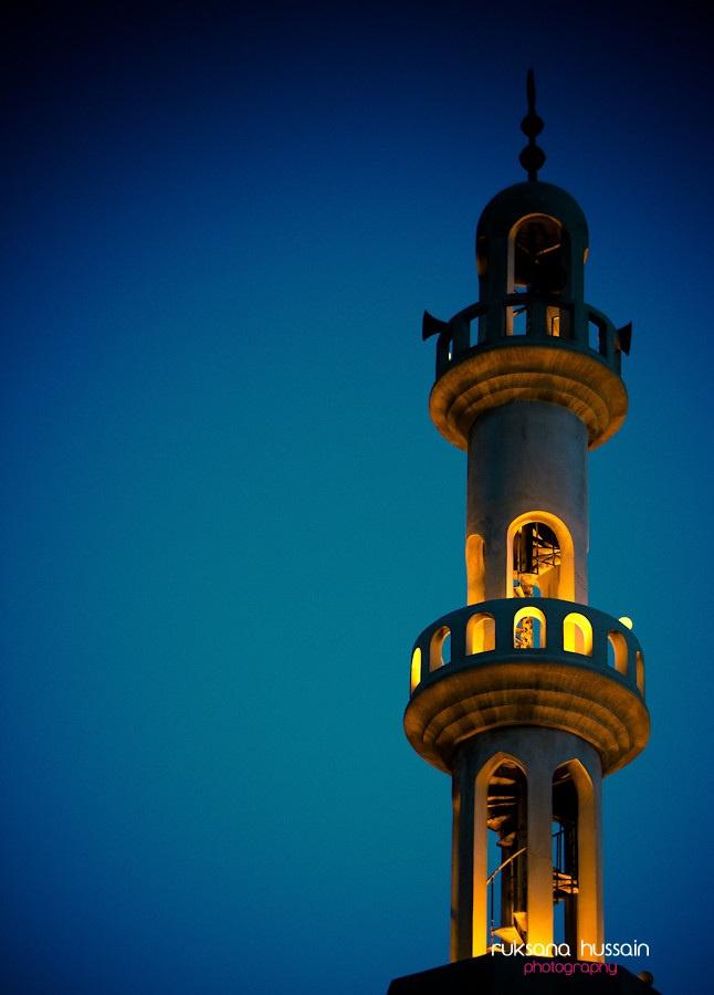 A minaret lit up during sunset prayer time (Maghrib prayers) in  Dubai.