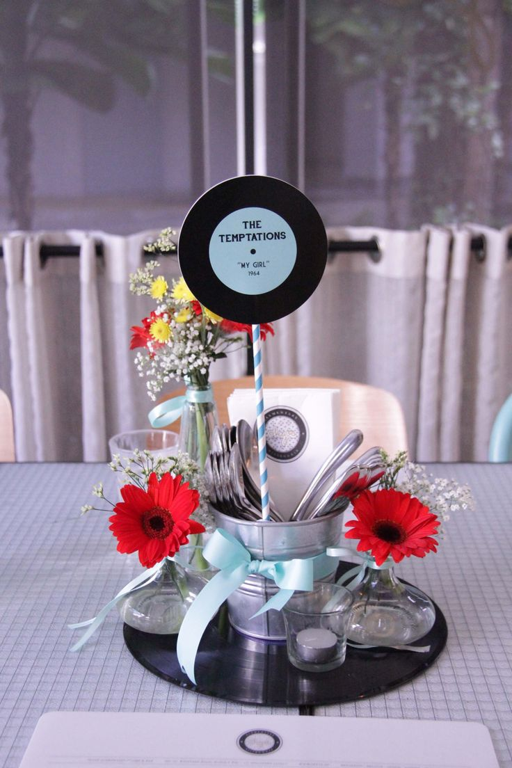 This centerpiece feels full, with height and depth, but not too busy. The two flowers make a big statement as the pop of color. Also...USEFUL for holding silverware and napkins...
