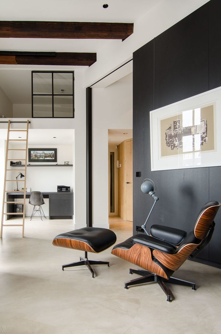 This open-concept Amsterdam loft features soaring 15-foot ceilings, an Eames lounge chair and ottoman, and a Jielde light. Throughout the home, Standard Studio architects Wouter Slot and Jurjen van Hulzen favored raw materials, including concrete, oiled oak, and hot-rolled steel, all of which complemented the original space's industrial feel. Tucked smartly underneath the loft, a compact home office features functional built-in shelving and an Eames DSR chair.