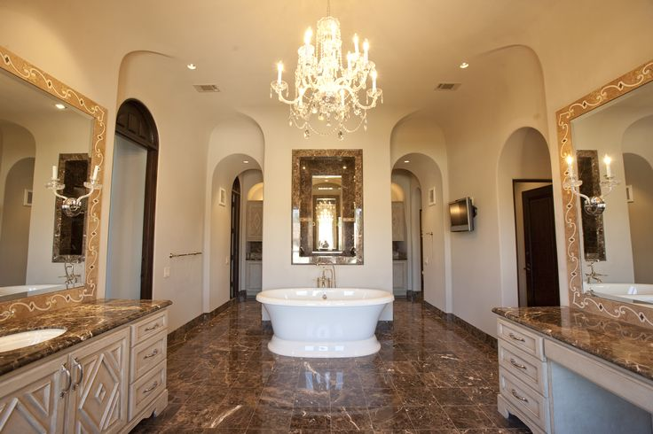 Dark marble contrasting with the white finishes! Look at the amazing curved arches and the lights reflecting in the well placed mirrors. #tiles #bathroom #chandelier #freestanding #bathtub