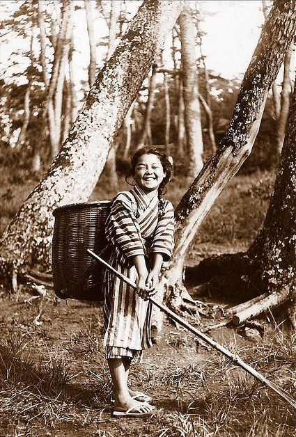 Smiling country girl raking leaves. Old Japan.