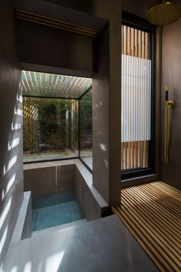 Glass walls and roof enclose this bathing area, offering views to the bamboo, planting and gravel that make up the property's private garden.