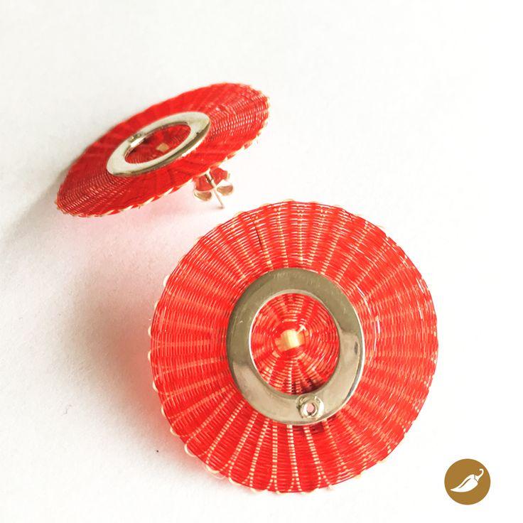 Aro tejido en crin en el que se destaca argolla en plata, la cual sostiene, da firmeza y sirve de base para el gancho del aro. Monoco es la precursora de la incorporación de la artesanía en crin en la joyería contemporánea. La diseñadora rescata este patrimonio inmaterial y lo incorpora en la joyería, fusionando el diseño y la artesanía. Autor: Monoco Dimensiones: Disco 3,5 cm de diámetro. Colección: Rari. Materiales: Plata, cobre y crin. Color: Rojo. Pieza única: No.