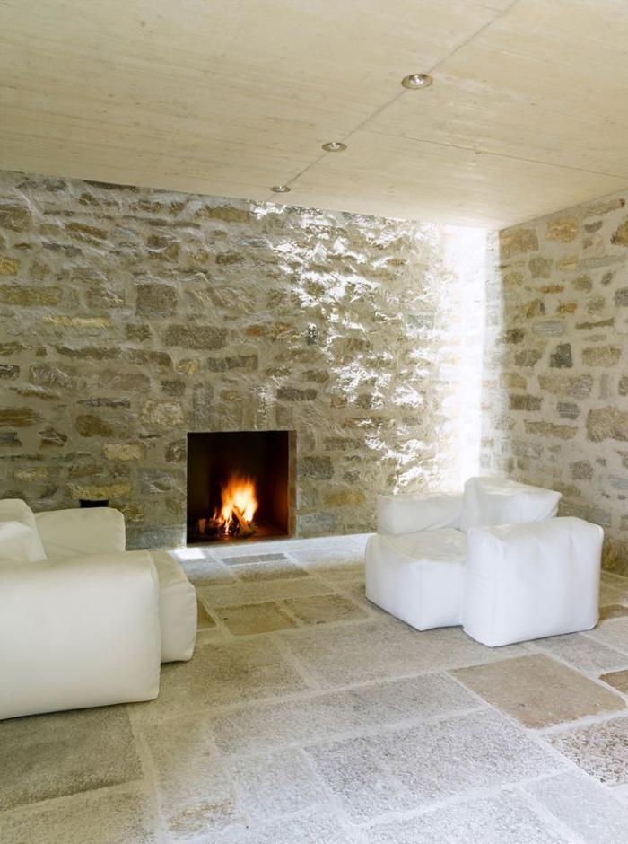 pierre apparente, parement mural en pierre, cheminée murale minimaliste et fauteuils modulaires