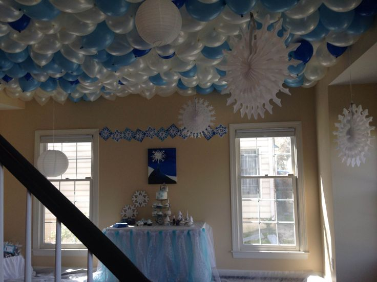 """FROZEN birthday party- April 2014. I covered the ceiling with balloons, hung paper snowflakes and lanterns, covered the floor in white Filato paper (looks like snow), made an """"Elsa's cape"""" tulle table skirt, painted a background Elsa scene on canvas and made theme cake/cupcakes."""
