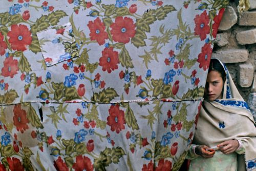 """""""reblololo:  An Afghan refugee girl stands in the doorway of her home in a slum area on the outskirts of Islamabad, May 7, 2012. (Muhammed Muheisen/Associated Press) #  """""""
