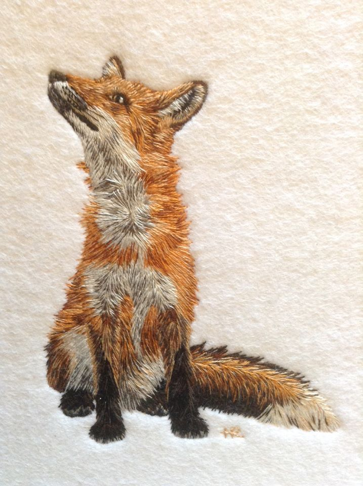 """Helen Richman combines her love for wildlife and embroidering in her work. Helen first draws her design onto tissue paper to tack it onto white felt, with the resultant tacking stitches becoming her guide. She then employs a hand embroidery technique called """"silk shading"""" using stranded cotton threads. Each needle will have one strand and Helen will have up to 10 needles being used at the same time. She then builds up the texture and colour of the fur slowly, creating a few stitches at a…"""