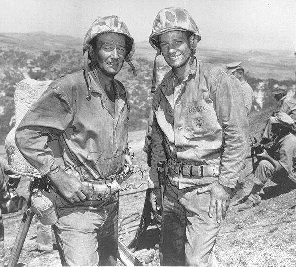"Iwo Jima flag raiser John Bradley with John Wayne during the filming of Wayne's classic war film, ""The Sands of Iwo Jima."" Bradley, along with Ira Hayes and Rene Gagnon, played himself. Bradley, a medic and civilian mortician, struggled with PTSD his entire adult life and rarely talked about the war after the film was released. This suffering veteran, directly linked to our country's greatest war actors, symbolizes the void between Hollywood and the sad realities of war."