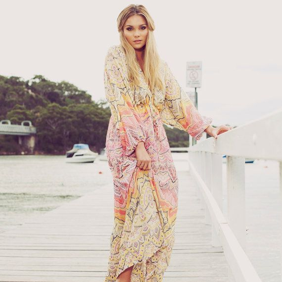 This light weight, floor length bohemian dress is so stunning to wear. it flows like no other and the shape is unlike anything you have seen. The colours and patterns of the fabric make this a stand out piece. You can tie the drawstring so it sits under the bust to reveal less or place it on the waist to really accentuate the deep-v. The skirt has beautiful volume and the cinching that the drawstring creates gives the dress and wearer amazing shape. The wide flared sleeves give this dress a…