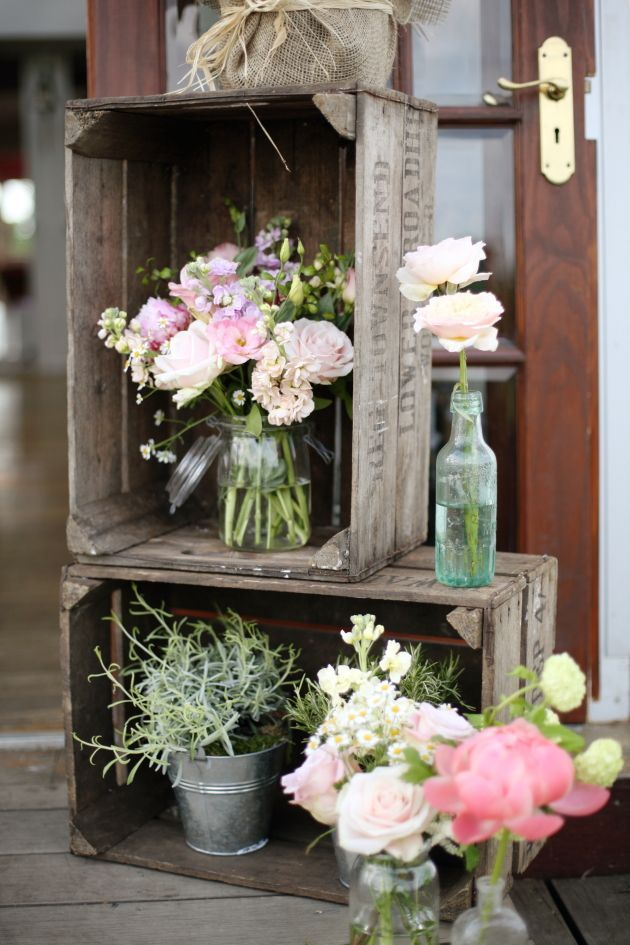 Stacked wooden crates, eclectic pots and vases with flowers - wedding flowers have never looked so rustic. Get more wedding inspiring at www.redonline.co.uk