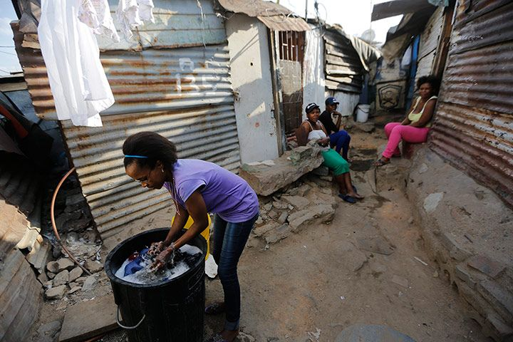 A woman washes her family's clothes in a dustbin in a side alley as her friends look on. Credit: Kim Ludbrook/EPA