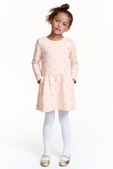 Jurk van joggingstof: CONSCIOUS. Een jurk van joggingstof van biologisch katoen met een glitterprint. De jurk heeft lange mouwen, een naad in de taille en steekzakken.