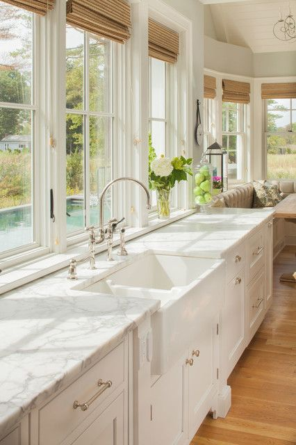Style ideas for any large seaside style u-shaped eat-in cooking area in Ny with a farmhouse sink, recessed-panel cabinets, white cabinets, marble countertops, white backsplash, stainless steel appliances, light hardwood floors and an island.