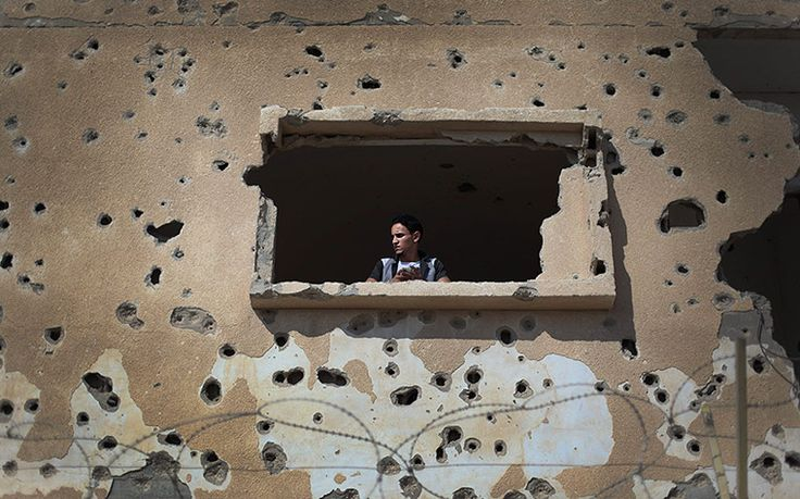 Rafah, Gaza: A Palestinian man looks out from a destroyed house near the border crossing with EgyptPhotograph: Ali Ali/EPA