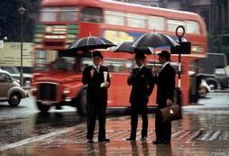 London, 1964. Three gentlemen wait for a bus in the rain on Hyde Park corner in London.