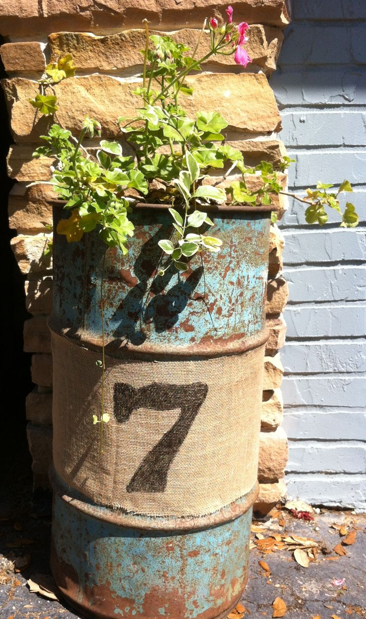 Needful Salvage...chipped & peeling blue metal container...wrapped with burlap & painted with No. 7...flowers.Do this behind the shed with the house numbers on it!!