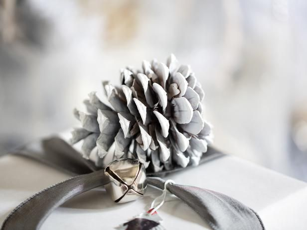 Give ordinary pinecones a snowy, frosted look by lightly misting with white spray paint along the entire body. Once dry, layer whitened pinecones onto branches either with rope added as hangers or simply placed loosely throughout the tree.  #HolidayHouse