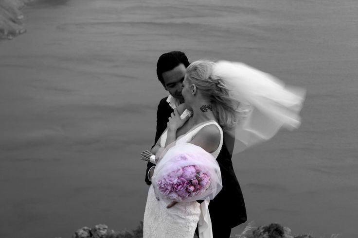 wedding photoshooting caldera cliff Santorni Greece couple in love pink bouquet