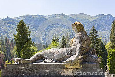 Antique stone woman statue on pedestal in the garden of Peles castle in Sinaia, Romania.