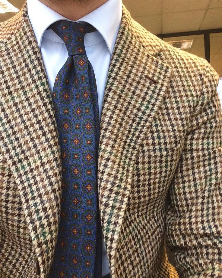 Light brown houndstooth tweed jacket, light blue shirt, blue tie