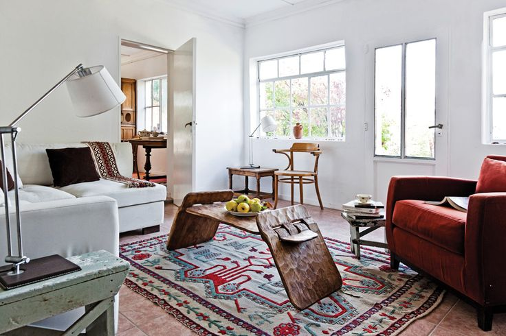 Living de una cálida casa patagónica con paredes y marcos pintados de blanco, mesa central de madera misionera y sillón de un cuerpo en color bordó.