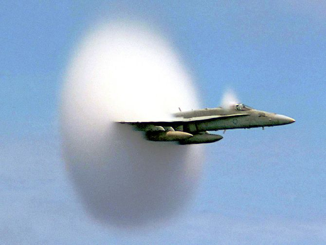 A cloud forms as this F/A-18 Hornet aircraft speeds up to supersonic speed.