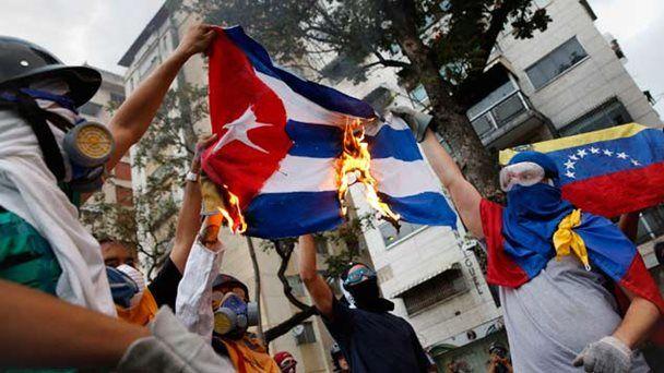 Manifestantes queman la bandera de Cuba