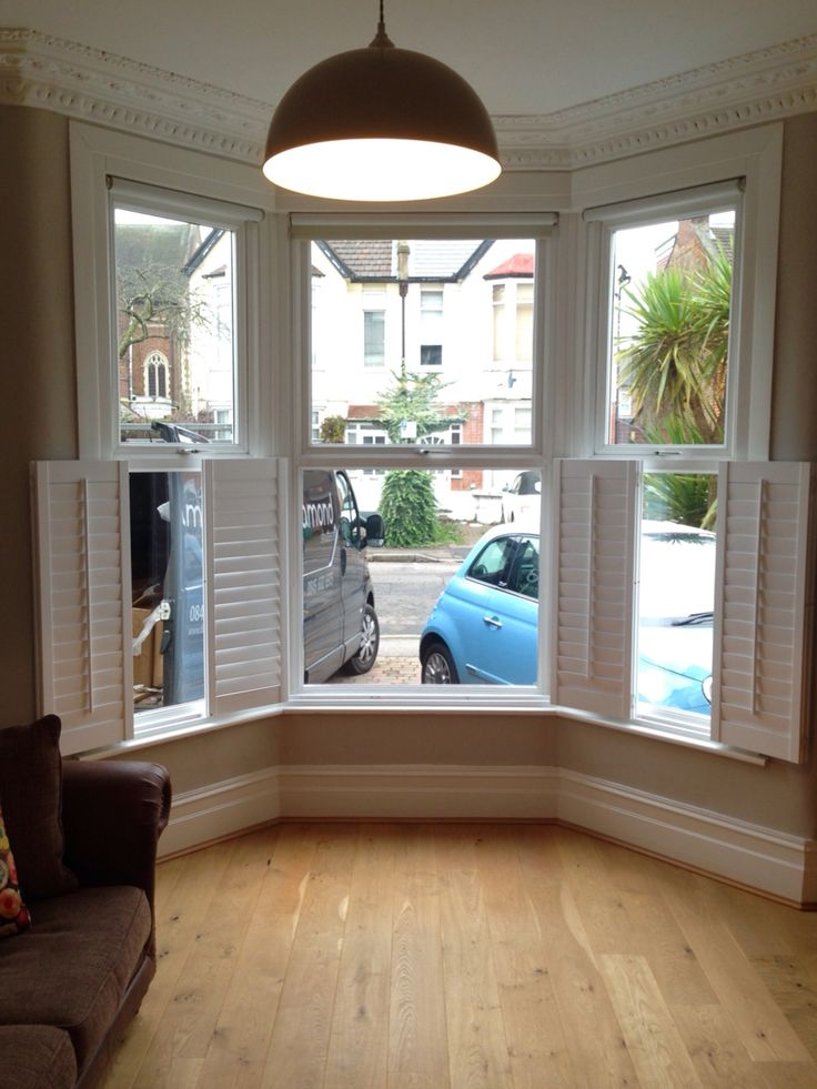 Cafe style shutters opened on a Victorian bay window