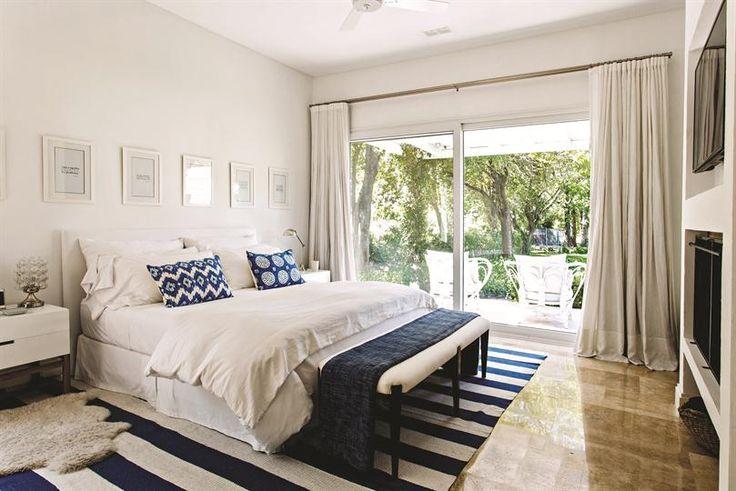 El cuarto principal tiene mucha frescura, los colores blanco y azul son los dominantes, llevándonos a un ambiente muy veraniego. Las cortinas livianas sobre el gran ventanal permiten apreciar el jardín. La alfombra tejida con gruesas rayas aporta calidez.. Foto: Silvio Zuccheri