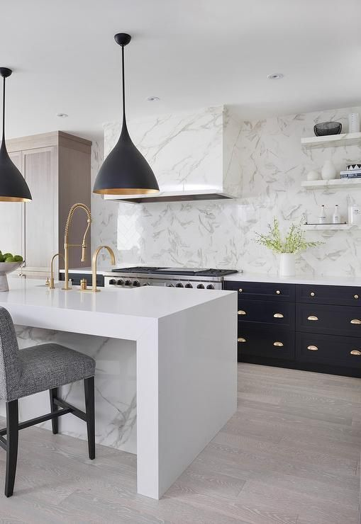 Next to taupe oak paneled pantry cabinets, black cabinets accented with brass hardware and a white marble countertop are located flanking a stainless steel dual oven range positioned beneath a white marble clad hood mounted to a white marble slab backsplash beside floating marble shelves.