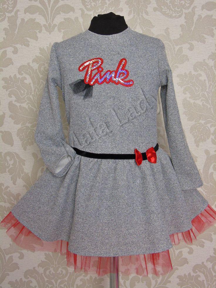 Bajeczna sukienka Pink w odcieniu szarości, delikatnie rozkloszowana. Dół sukienki to połączenie materiału bawełnianego z tiulem oraz koronką, odszyty podszewką. Sukienka posiada długi rękaw oraz kryty zamek z tyłu kreacji. Przód sukienki ozdabia czarny pasek z czerwoną kokardą.  Sukienka dostępna z dodatkami w kolorze różu lub czerni.