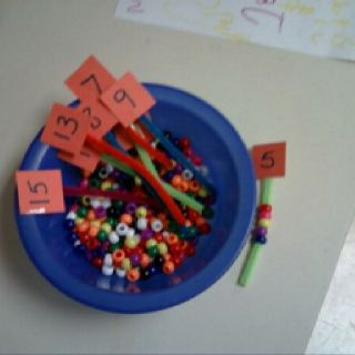 Pipe cleaners cut short with a number taped to the end.  Have the kids feed the same number of pony beads onto the pipe cleaners. Great for kinder!